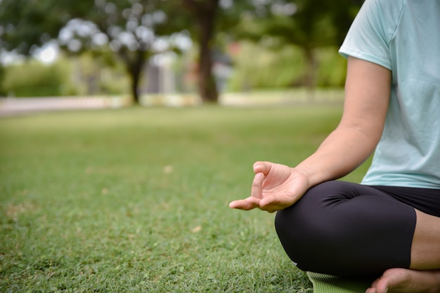 La fine su delle mani della donna fa l'yoga all'aperto nel parco.