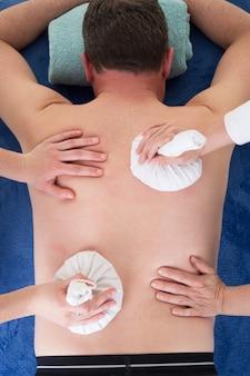 La fine su delle mani femminili di massaggio dà la terapia calda della palla delle erbe per l'uomo