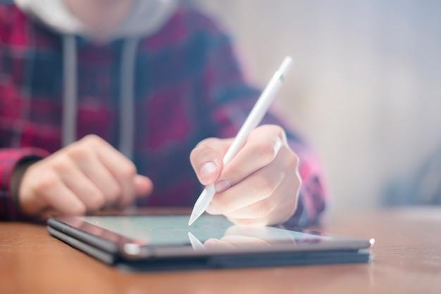 La fine sulla mano con la penna digitale disegna sulla compressa