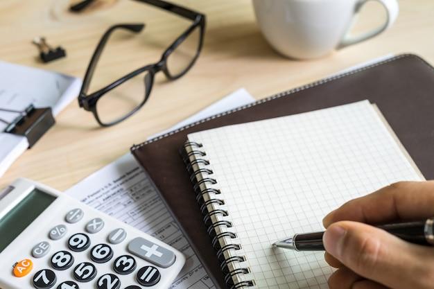 La fine sulla mano del giovane facendo uso del calcolatore e la scrittura fanno la nota sull'ufficio dello scrittorio