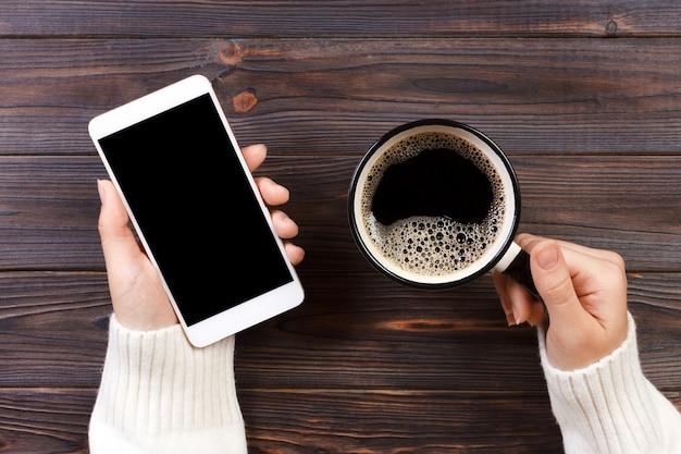La fine sulla mano dell'uomo di affari tiene lo smart phone con lo schermo isolato il nero sopra fondo e caffè di legno
