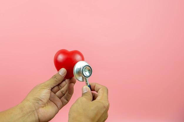 La fine sulla mano facendo uso dello stetoscopio sta controllando un cuore. concede un esame fisico per l'assistenza sanitaria e l'assicurazione medica.