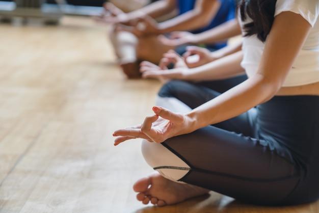 La fine sulle mani della donna pratica l'yoga e la meditazione nella posa del loto al club di forma fisica