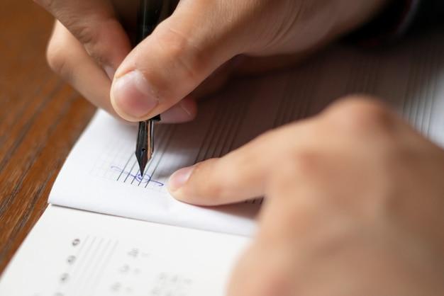 La fine sulle mani dello studente annota le note di musica su classe a scuola