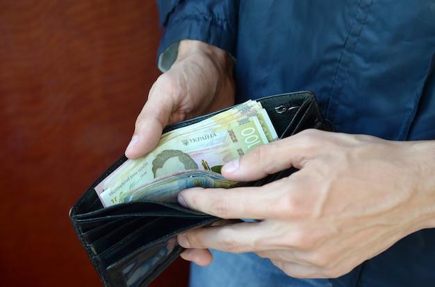 La fine sulle mani maschii ha aperto il portafoglio o la borsa con la grivna ucraina di valuta dei soldi