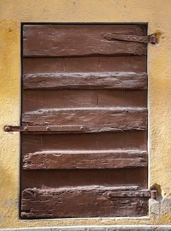 La finestra di legno marrone rustica shutters con il fondo di giallo della parete di pietra.