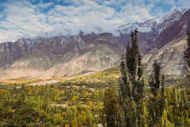 La foresta verde con le nuvole ha coperto i picchi di montagna ricoperti neve in hunza, pakistan.