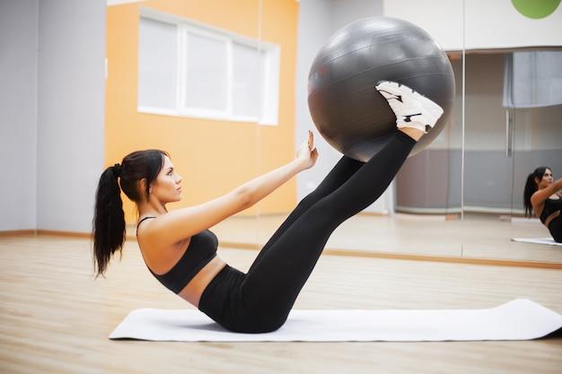 La forma fisica, il fronte sorridente della bella donna gode di risolve con la palla adatta nella forma fisica - concetto di stile di vita e di sport.