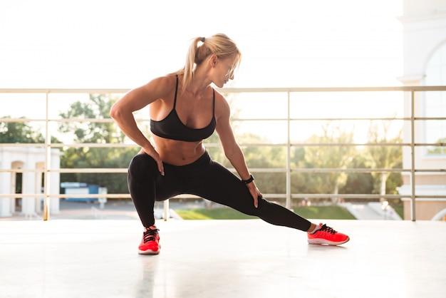 La forte giovane donna di sport fa l'allungamento di sport