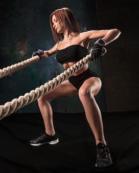 La forte giovane donna tirando la corda in una palestra