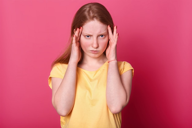 La foto a mezzo busto della ragazza teenager triste con un terribile mal di testa, ha gravi problemi a scuola, indossa casualmente, in posa sul rosa. espressioni facciali e concetto di emozioni della gente.