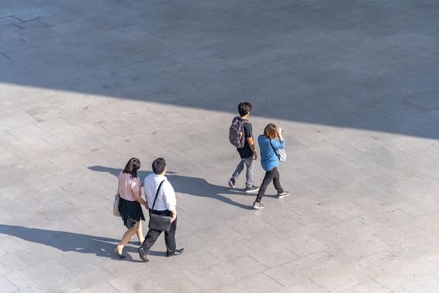La foto aerea della gente cammina sul passaggio pedonale davanti al centro commerciale nella città