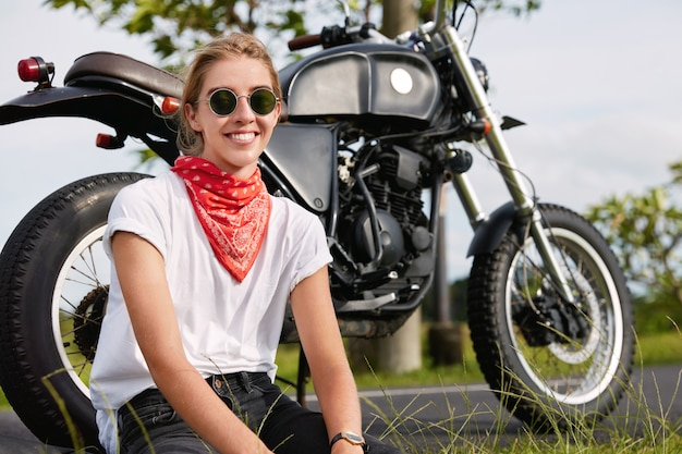La foto del motociclista femminile allegro si siede vicino alla motocicletta nera all'aria aperta, indossa abiti eleganti, viaggia in un luogo di campagna sconosciuto contro una scena meravigliosa. concetto di stile di vita all'aperto.