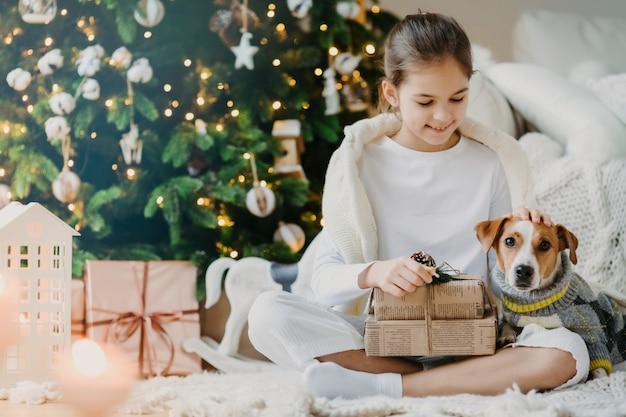 La foto del piccolo bambino adorabile si siede le gambe incrociate sul pavimento, il cane di razza degli animali domestici ha ricevuto i regali di natale dai genitori che celebrano insieme il nuovo anno. kid gode le vacanze con jack russell terrier apre regali
