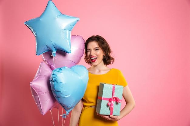 La foto del primo piano della ragazza allegra di compleanno con le labbra rosse sbatte le palpebre un occhio mentre tiene il contenitore e gli aerostati di regalo