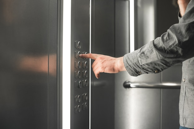 La foto del primo piano di una mano sceglie un piano nell'ascensore.