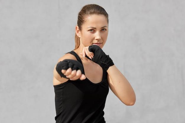 La foto del pugile femminile in posizione difensiva, sembra feroce, vestita in maglietta nera, bende sulle mani, pronta a combattere con l'avversario, si leva in piedi su grigio. concetto di persone e boxe