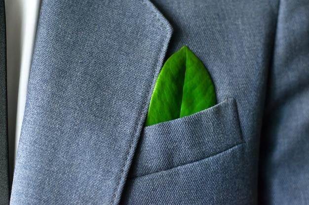 La foto dell'uomo d'affari in giacca e cravatta con una foglia in tasca