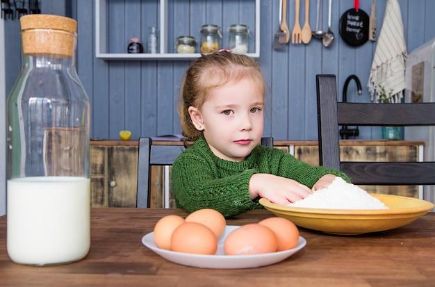 La foto della bambina tira le sue mani alla farina