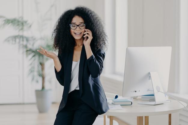 La foto della donna di affari prospera perplessa chiama il partner, alza il palmo, tiene il telefono cellulare