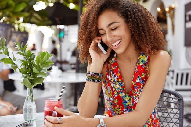 La foto della donna riccia dalla pelle scura positiva indossa una camicetta alla moda, ha una piacevole conversazione telefonica durante il riposo nella caffetteria all'aperto