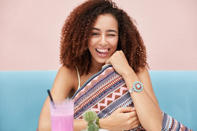 La foto della femmina dalla pelle scura afroamericana divertente allegra ha i capelli crespi, sbatte le palpebre e mostra la lingua