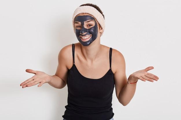 La foto della giovane donna con il sorriso affascinante che distende le palme da parte, mostra un gesto impotente, indossa una maschera facciale nutriente per ridurre le rughe, pone contro il muro bianco.