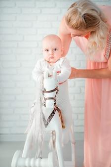 La foto della madre fa rotolare il suo piccolo figlio su un cavallo giocattolo