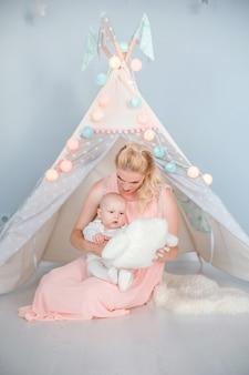 La foto della madre gioca con il figlio in una stanza vicino a una tenda per bambini