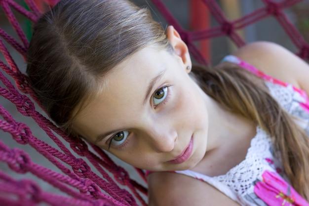 La foto della ragazza teenager si trova su hammock durante il giorno di estate e l'esame della macchina fotografica