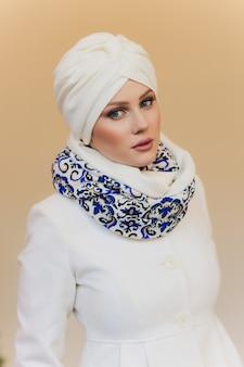 La foto della signora araba sicura di sé in hijab, ti mostra la strada giusta, indica lo spazio vuoto con entrambe le dita anteriori, invita ad andare lì, promuove lo spazio della copia. dai un'occhiata a me.