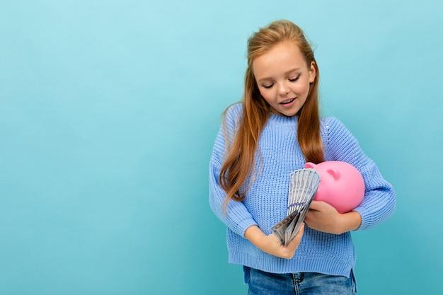 La foto di copyspace di bella ragazza alla moda in un maglione su un fondo blu con un porcellino salvadanaio conta i soldi