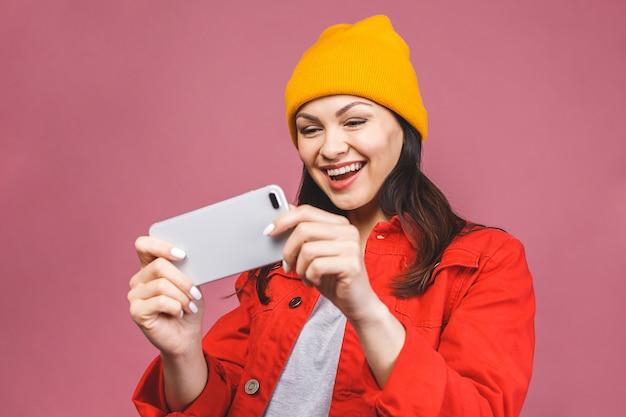 La foto di giovane donna caucasica emozionale gioca per telefono. guardando da parte. isolato sul muro rosa.