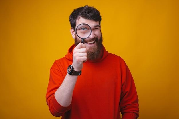 La foto di un giovane uomo adulto felice sta guardando attraverso la lente d'ingrandimento su di te su spazio giallo.