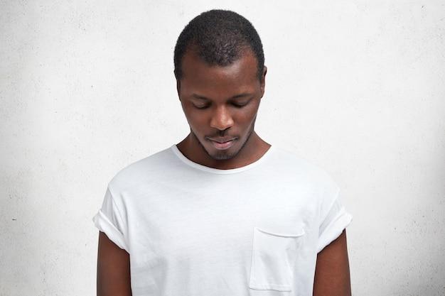 La foto di un maschio dalla pelle scura guarda in basso mentre nota qualcosa, vestito con una maglietta casual, pubblicizza un nuovo vestito, isolato su un muro di cemento.