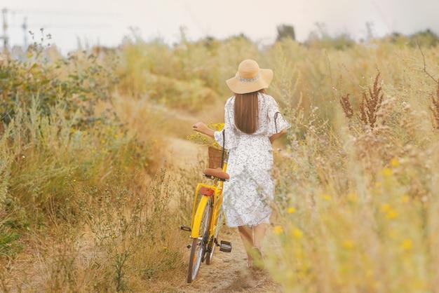 La foto di una giovane donna che indossa un abito bianco e un cappello sta camminando con la sua bicicletta gialla su un campo