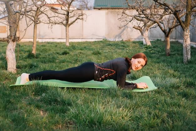 La foto laterale integrale di profilo della donna adulta fa l'esercizio della plancia e l'esame della macchina fotografica