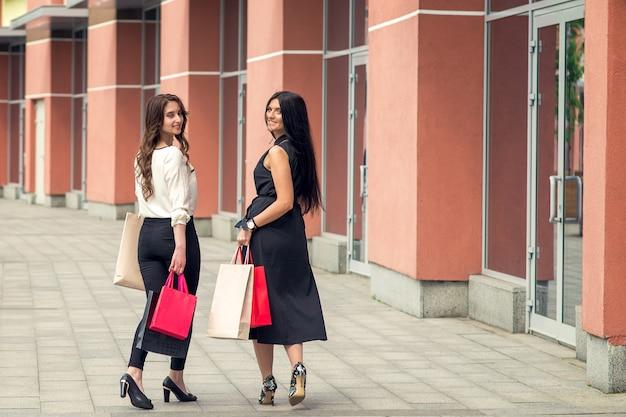 La foto posteriore di vista delle giovani donne sta posando con i sacchetti della spesa nella via.