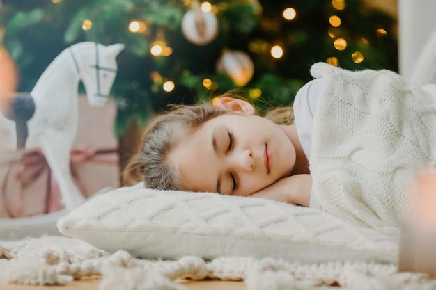 La foto ravvicinata del bambino piccolo attraente si trova sul pavimento, dorme vicino all'albero di natale o capodanno, riscalda con un maglione lavorato a maglia bianco, ha sogni piacevoli in serata. bambini, vacanze invernali, concetto di riposo