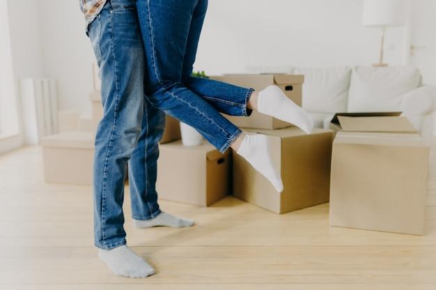 La foto ritagliata di un uomo premuroso solleva la moglie, indossa jeans e calze, si è appena trasferita in una nuova casa, si posa intorno a scatole di cartone sul pavimento, eccitata di muoversi. coppia irriconoscibile trasferirsi in un nuovo posto