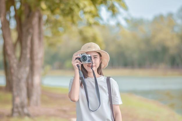 La fotocamera asiatica delle donne viaggia e scatta foto natura