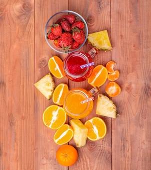 La fragola fresca e cocktailes arancione con frutta su un fondo rustico in legno.