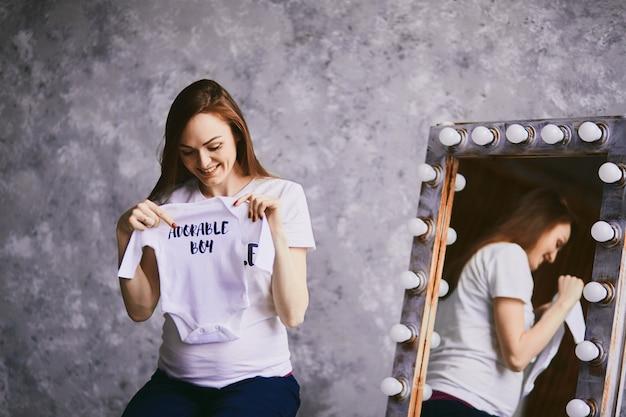 La futura mamma tiene una maglietta per bambino
