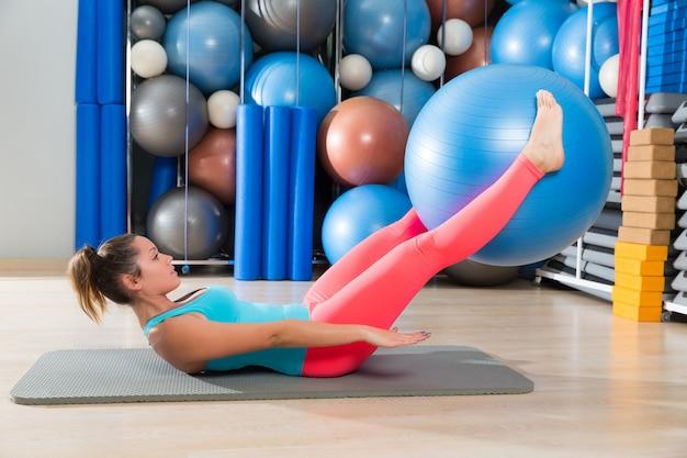 La gamba della sfera svizzera della donna di esercitazione di ab solleva pilates