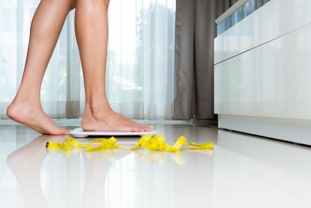 La gamba femminile sta calpestando le scale bianche con nastro adesivo di misura