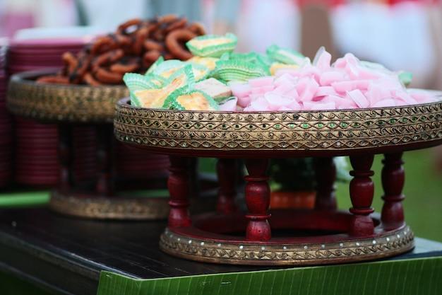 La gelatina rosa dei dessert dolci tailandesi nel cuore ha modellato e bigné della banana sul canestro del rattan nel giardino di nozze