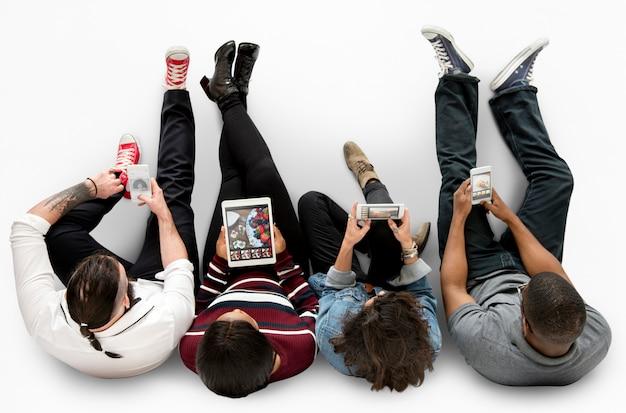 La gente adulta usa lo studio del telefono cellulare della compressa