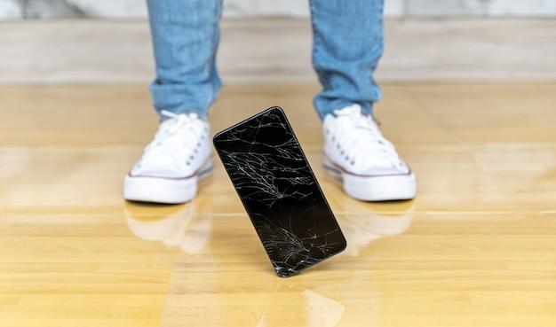 La gente cade smartphone sullo schermo rotto del pavimento