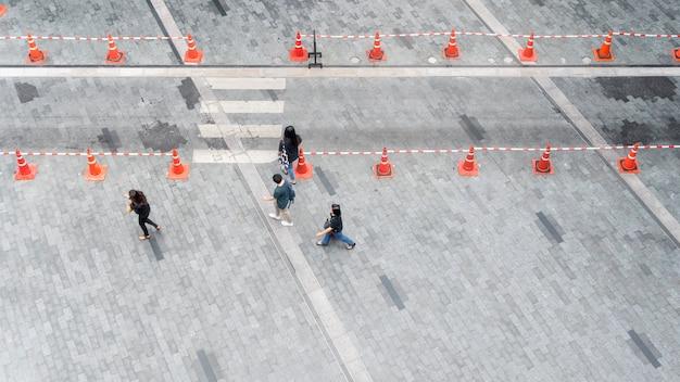 La gente cammina sul marciapiede pedonale della città su pavimentazione in cemento con il gruppo di moda uomo e donna