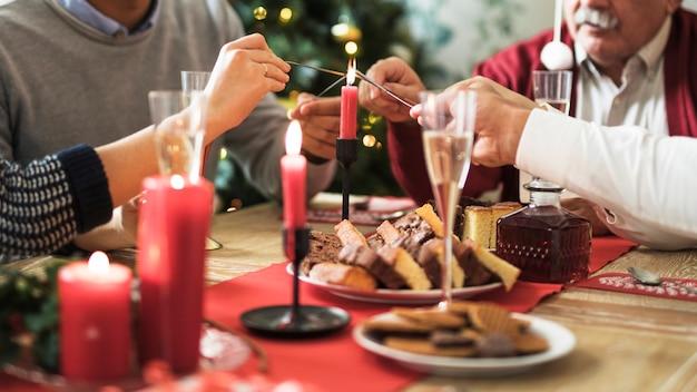 La gente che accende il fuoco del bengala al tavolo festivo